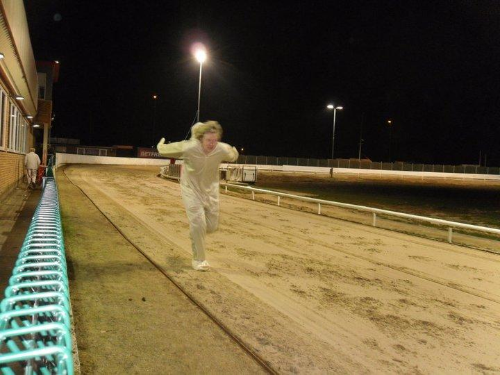 Party boy in full dog outfit running the track